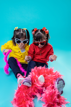 Red festive boa. Little twin sisters having holiday mood while playing with pink boa being dressed in funky glasses