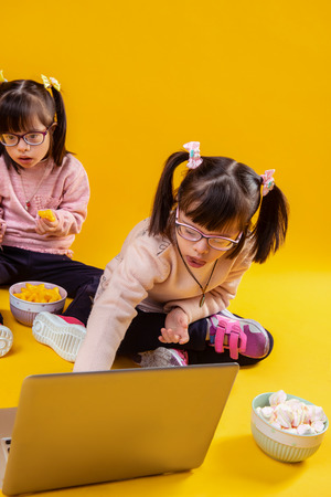 Eating from bowl. Two sisters with mental disorder playing with laptop while being surrounded by snacks