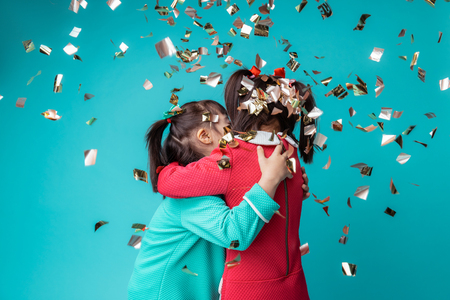Confetti covering them. Two cute girls with mental disorder being happy together while celebrating holidays