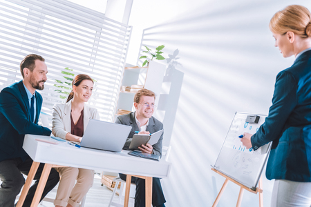 Working plan. Delighted positive colleagues listening to their boss while having a meeting Stock Photo