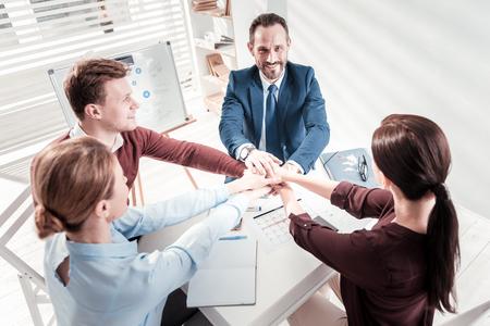 Perspektive Geschäft. Draufsicht auf optimistische vier Kollegen, die sich treffen und Händchen halten Standard-Bild