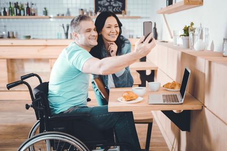 Le sourire. Joli couple heureux faisant une photo ensemble dans un café Banque d'images