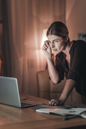 Total concentration. Attractive female freelancer touching glasses and using laptop