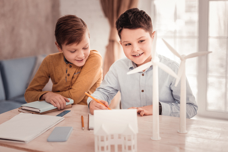 Cute schoolboys. Two cute pleasant looking schoolboys feeling very busy while completing their home assignment Stock Photo