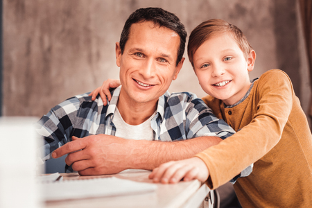 Father and son. Smiling broadly father and son feeling wonderful and amazing while looking at their beautiful mother