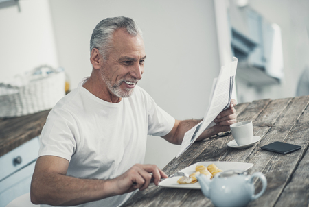 Morning crepes. Grey-haired smiling contended businessman eating delicious crepes in the morning at home