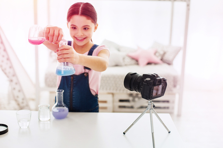 stand. Smiling beautiful little using camera stand while filming chemistry experiment in her living room