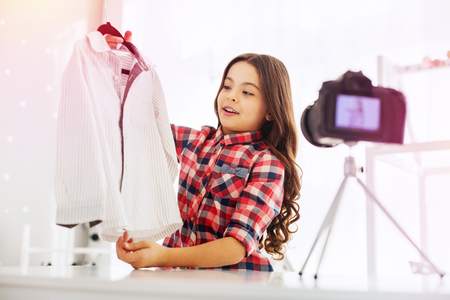 about clothes. Dark-haired beaming little fashion feeling really joyful while filming about school clothes Stockfoto