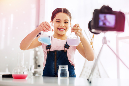 Funny girl. Funny girl fond of chemistry filming video while making experiment in front of her camera