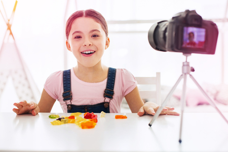 Food . Little funny food telling her followers about favorite sweets and candies sitting in front of camera Stockfoto