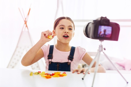 Girl eating. Funny dark-eyed girl wearing jeans jumpsuit sitting in front of camera eating gummy bears