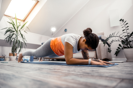 Stretching workout. Serious assertive woman doing strap during active workout session in attic apartments