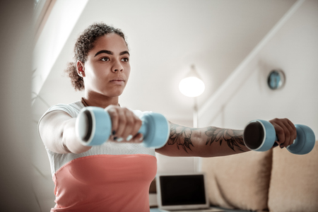 Woman doing squats. Resolute good-looking serious woman putting forward hand while holding dumbbells during active workout