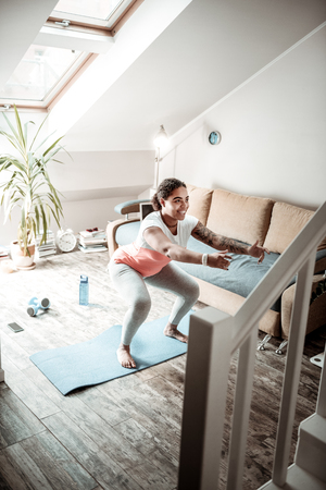 Pumping up legs. Cheerful young woman doing special exercises for fitting lower body and rising her hands