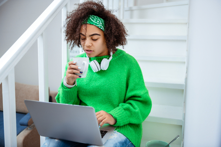 Girl taking pills. Fashionable good-looking female sitting on the stairs and drinking hot tea while holding laptop Stockfoto