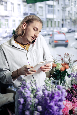 Busy at work. Concentrated blonde man looking at notes while standing between flowers
