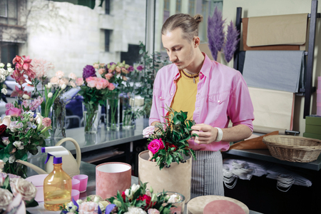 Favorite color. Kind man standing at his workplace and looking at flowers Reklamní fotografie