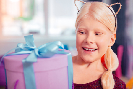 It is surprise. Beautiful blonde girl expressing positivity while staring at gift box