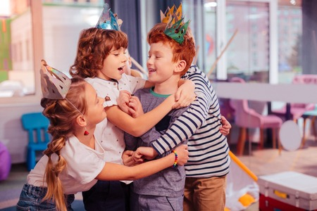 My cousin. Cheerful red-haired kid embracing his friend while laughing at joke