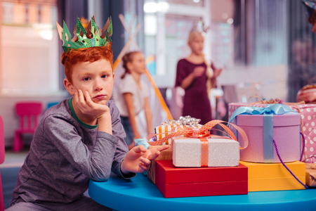 Want to play. Attentive man pointing at gift boxes and looking straight at camera