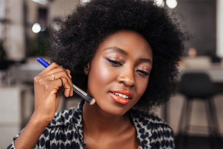 Makeup. Pretty african american woman with curly hair looking focused while trying a new concealer on her skin