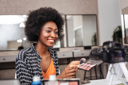 Online tutorial. Cute dark-skinned woman with coral lipstick smiling while conducting online tutorial