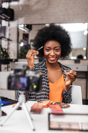 Eyebrows. Smiling dark-skinned woman wearing an orange top correcting eyebrows shape