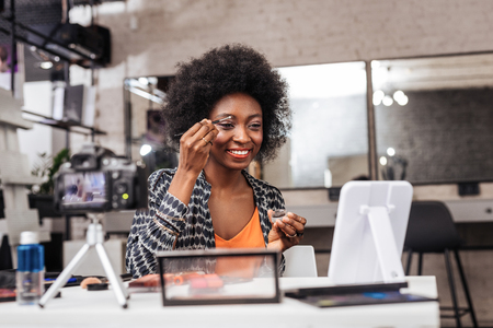 Video blogger. Smiling dark-skinned woman wearing an orange top demonstrating how to correct eyebrows