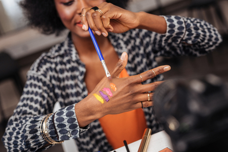 Beautiful dark-skinned african american woman with a gold bracelet demonstrating new swatches to the audience
