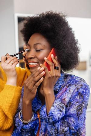 Nice eyeshadows. Stylist wearing a yellow thick sweater putting eyeshadows on models eyelids Imagens