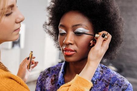 Mascara. Giovane stilista dai capelli biondi che indossa smalto nero che mette il mascara sulle ciglia dei modelli