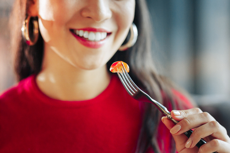 Piece of tomato. Close up of dark-haired woman smiling while eating little piece of tomato Фото со стока