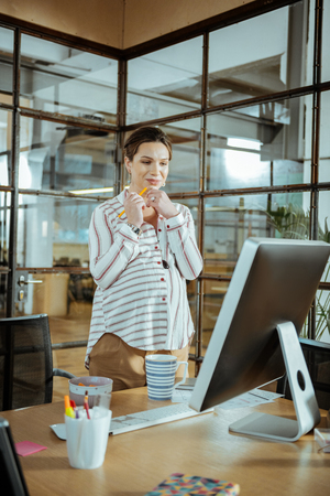 Pregnant businesswoman. Young pregnant businesswoman wearing stylish blouse working in modern office