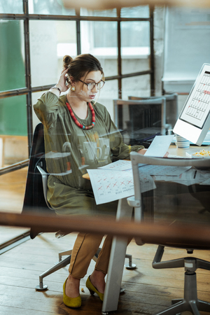 Work in office. Pregnant woman wearing khaki dress feeling busy while working in her office