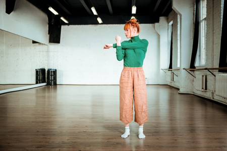 In the gym. Red haired young girl wearing a green turtleneck doing exercising in a gym