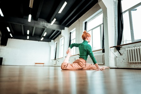 Doing leg-split. Professional yoga instructor with red hair wearing a green turtleneck looking focused while doing leg-split Stock Photo