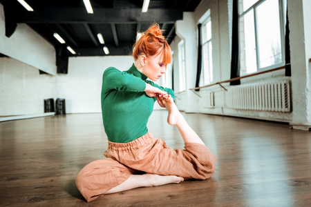 Feeling concentrated. Young red-haired yoga instructor with hair bun looking involved while doing yoga Imagens