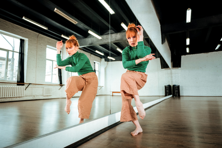 Modern dance. Beautiful professional modern dancer with red hair wearing a green turtleneck dancing near the mirror Stok Fotoğraf