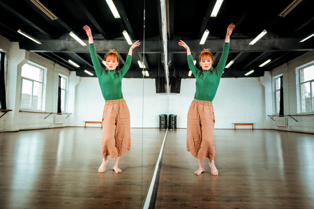 Beautiful dance. Cute red-haired dance teacher in a green turtleneck raising her hands while dancing in a studio
