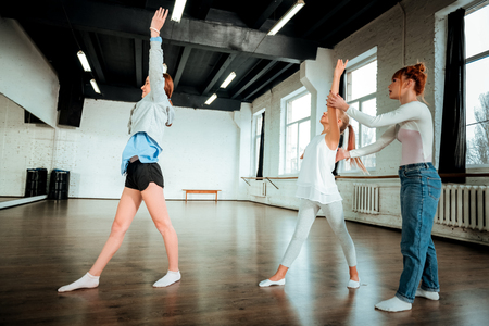 Movements. Professional modern dance teacher with red hair wearing jeans showing movements to her students Stock Photo