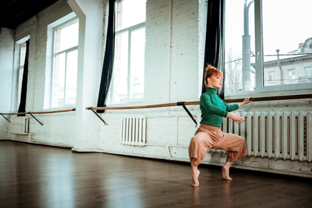 Sportive woman. Young professional modern dancer with red hair looking involved while training near ballet bar
