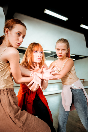 Arm stretching. Beautiful dance teacher with red hair and her students looking concentrated while doing arm stretching Banque d'images