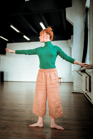 Graceful dancer. Young professional modern dancer with red hair looking graceful Stock Photo
