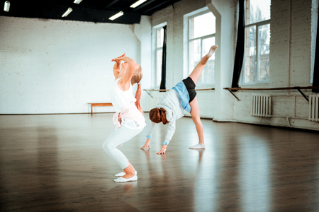 Expressive look. Blond teenager from generation z in white clothing looking expressive while dancing