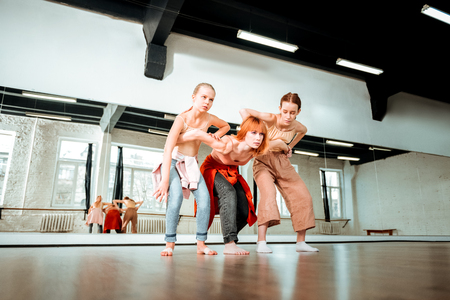 Working with a teacher. Two cute students of dance school looking serious while working with their teacher
