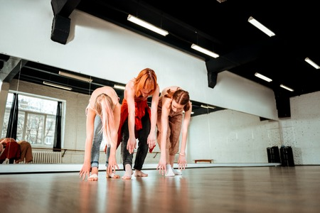 Legs swinging. Beautiful dance teacher with red hair and her students looking involved while swinging their legs