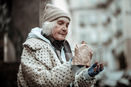 I am hungry. Sad aged woman looking at the food while feeling very hungry Imagens