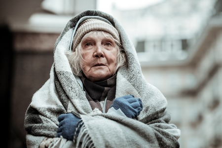 Feeling cold. Portrait of a cheerless aged woman while feeling cold
