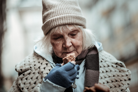 Feeling of hunger. Nice aged woman looking at the bread while wanting to eat it Banque d'images - 116095550