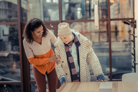 What would you like. Positive friendly woman showing her kindness while asking an elderly woman what she wants